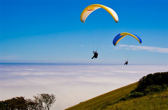 Two Hang gliders over beachy head sussex england showing a sea mist
